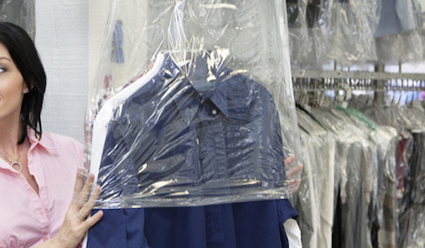 a lady turning to present dry cleaned clothes wrapped in see through bags to a customer