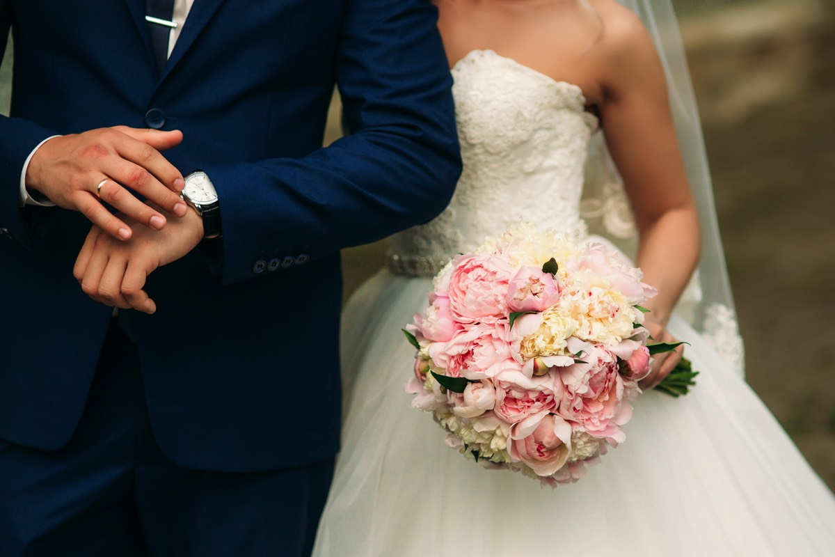 a man in a stylish suit and lady in a wedding dress carrying flowers