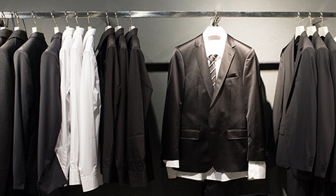 a row of similar black formal jackets and white shirts hanging on a rail. One jacket hangs forward complete with white shirt and tie on a rail