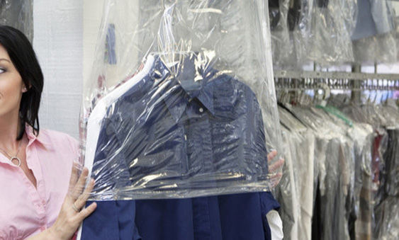 a dry cleaning staff member handling dry cleaning infront of rows of dry laundered clothes in see through palstic bags on a rail