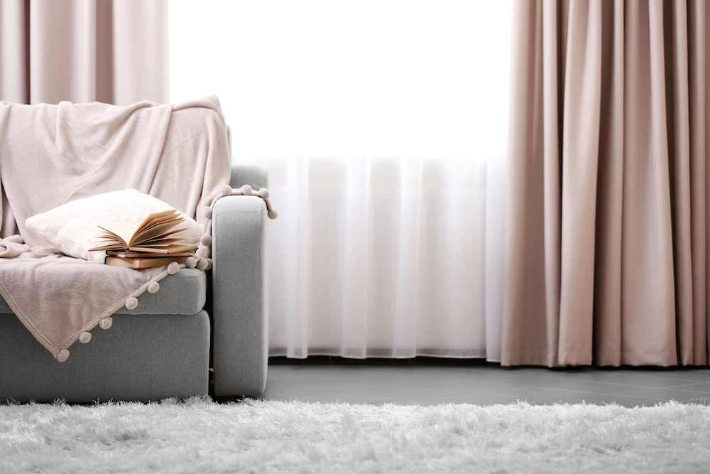 a interiior of muted light coloured room showing a sofa a throw a rug and some curtains