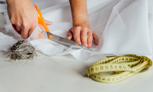 a seamstress or tailor cutting material for a wedding dress