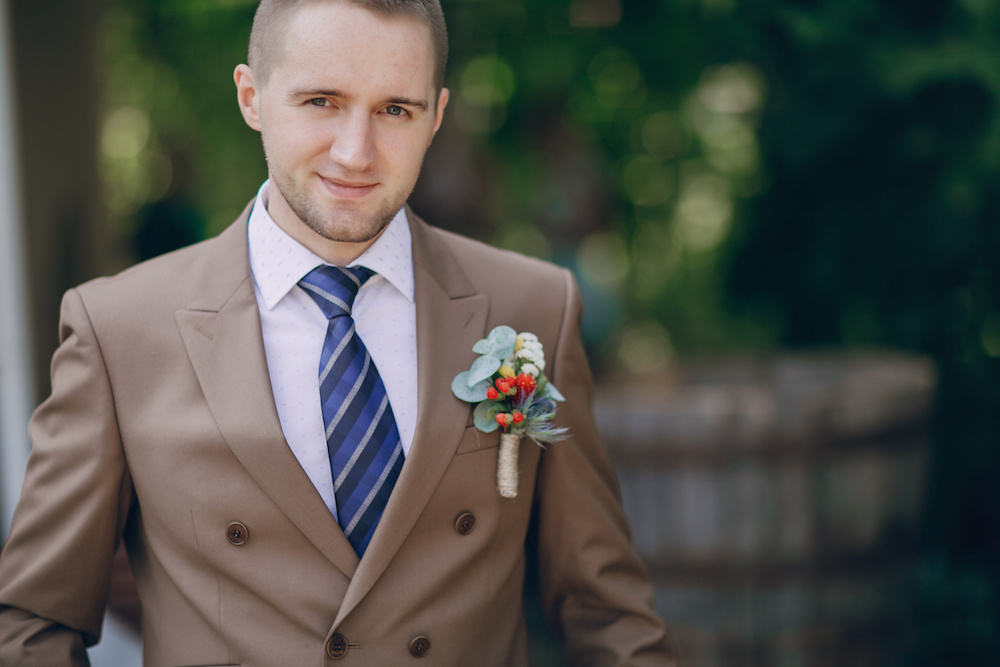 a young man in a suit with a flower for wedding